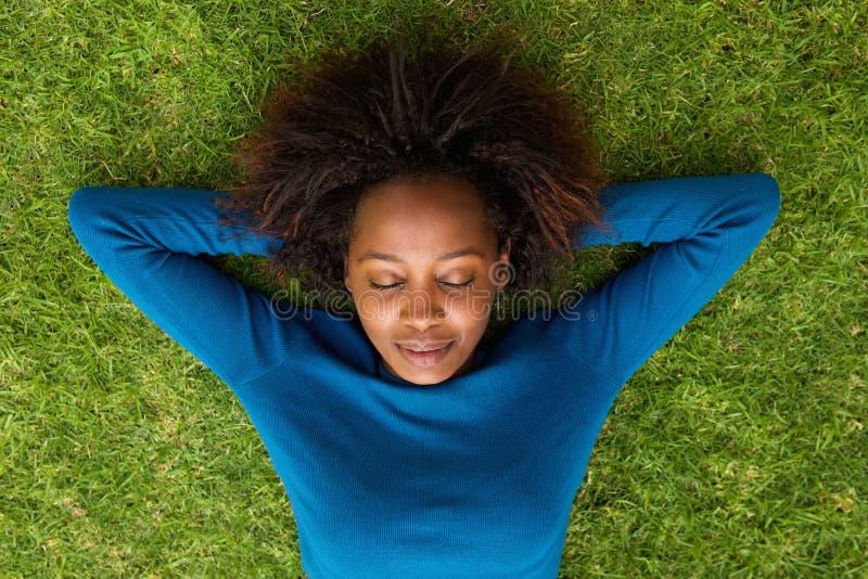 Junge afrikanische Frau, die auf dem Grasschlafen liegt lizenzfreies stockbild