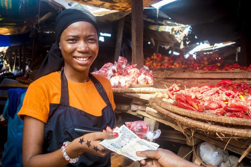 Junge afrikanische Frau, die Lebensmittel in einem afrikanischen Markt verkauft, sammelt Geld von einem zahlenden Kunden lizenzfreies stockfoto