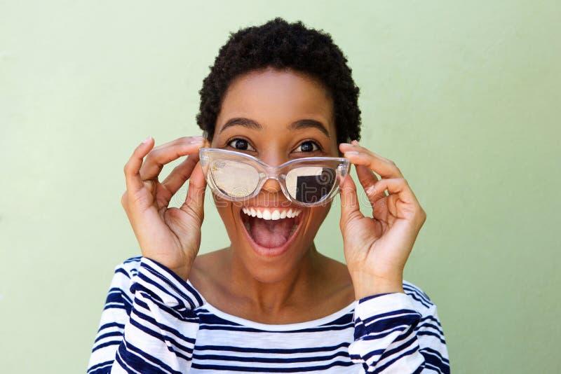 Junge afrikanische Frau, die mit Sonnenbrille gegen grüne Wand lächelt lizenzfreies stockfoto