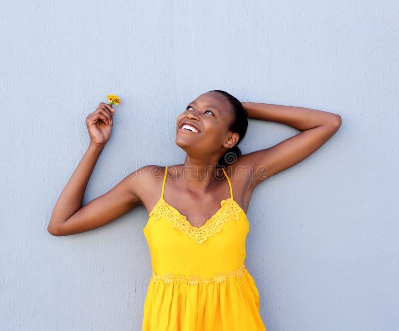 Junge afrikanische Frau im gelben Kleid eine Blume stockbild