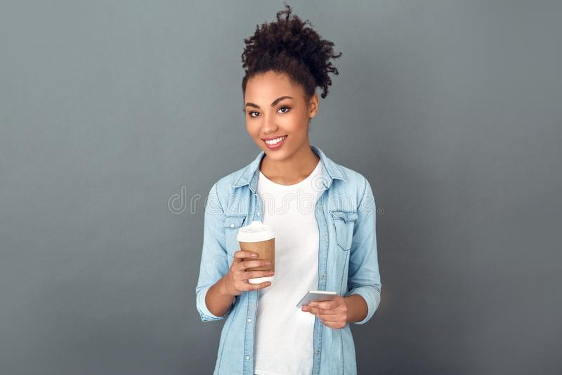 Junge afrikanische Frau lokalisiert auf dem zufälligen täglichen Lebensstil des grauen Wandstudios, der Kaffee hält lizenzfreie stockfotografie