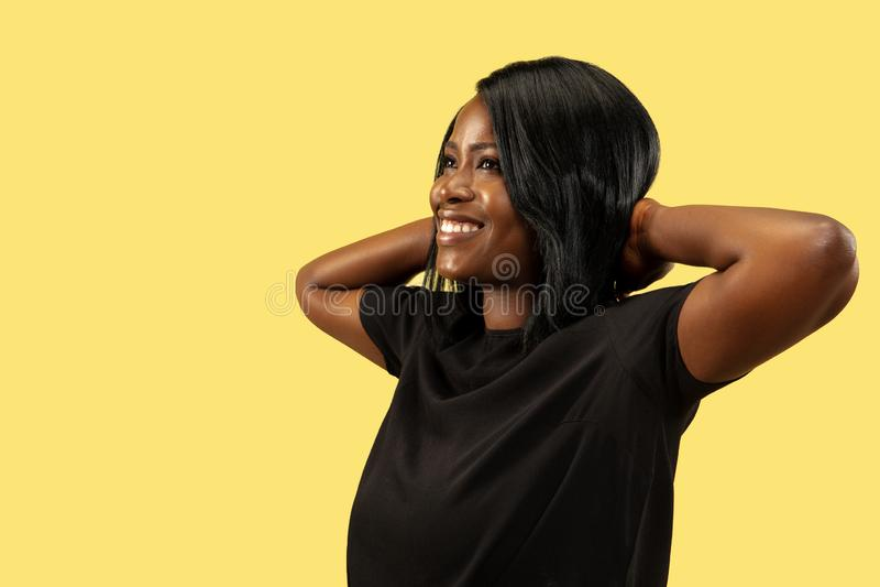 Junge afrikanische Frau lokalisiert auf gelbem Studiohintergrund, Gesichtsausdruck lizenzfreies stockbild