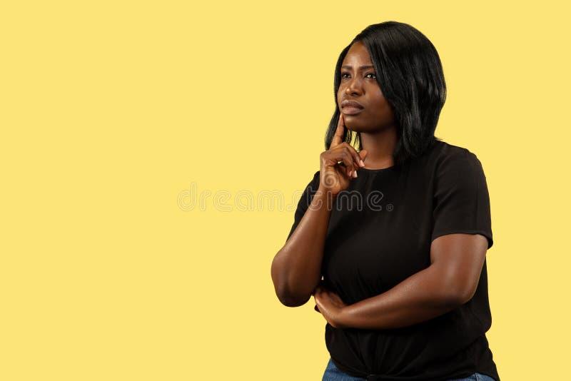Junge afrikanische Frau lokalisiert auf gelbem Studiohintergrund, Gesichtsausdruck lizenzfreie stockfotos