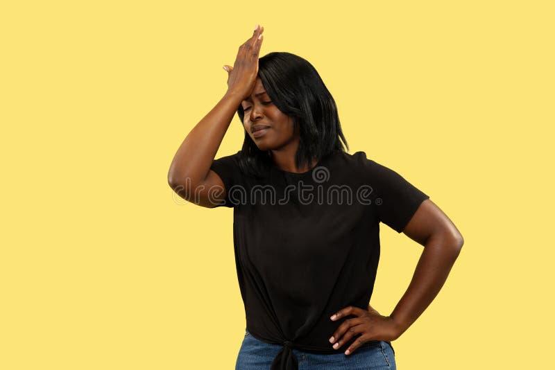 Junge afrikanische Frau lokalisiert auf gelbem Studiohintergrund, Gesichtsausdruck stockbild