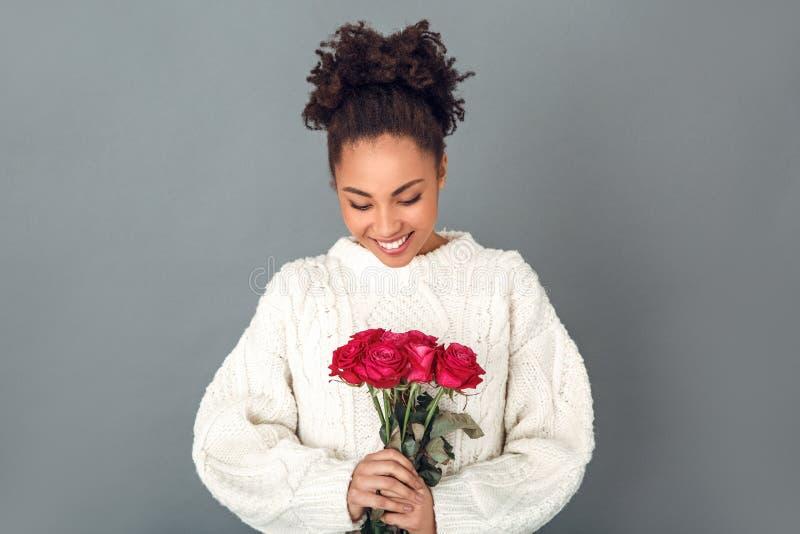 Junge afrikanische Frau lokalisiert auf grauem Blumenstrauß der roten Rosen des Wandstudiowinterkonzeptes stockfotografie