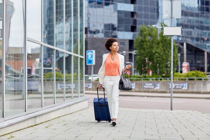 Junge afrikanische Frau mit Reisetasche in der Stadt stockfoto