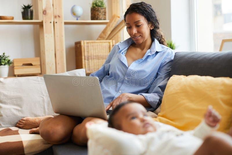 Junge afrikanische Mutter, die zu Hause arbeitet lizenzfreie stockbilder