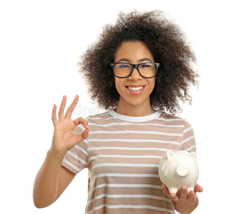 Junge afro-amerikanische Frau mit OKAYgeste der Sparschweinvertretung auf weißem Hintergrund Illustration 3d auf wei?em Hintergru lizenzfreie stockbilder