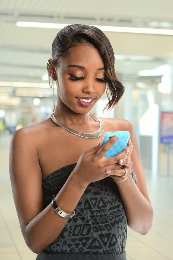 Junge Afroamerikaner-Frau, die Handy verwendet lizenzfreies stockbild