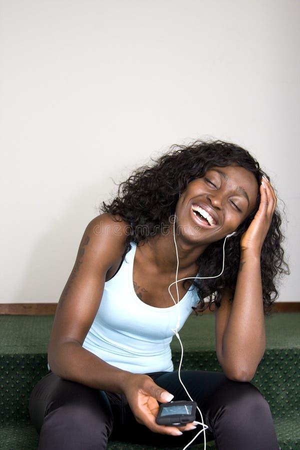Junge Afroamerikaner-Frau, die Musik hört stockfoto