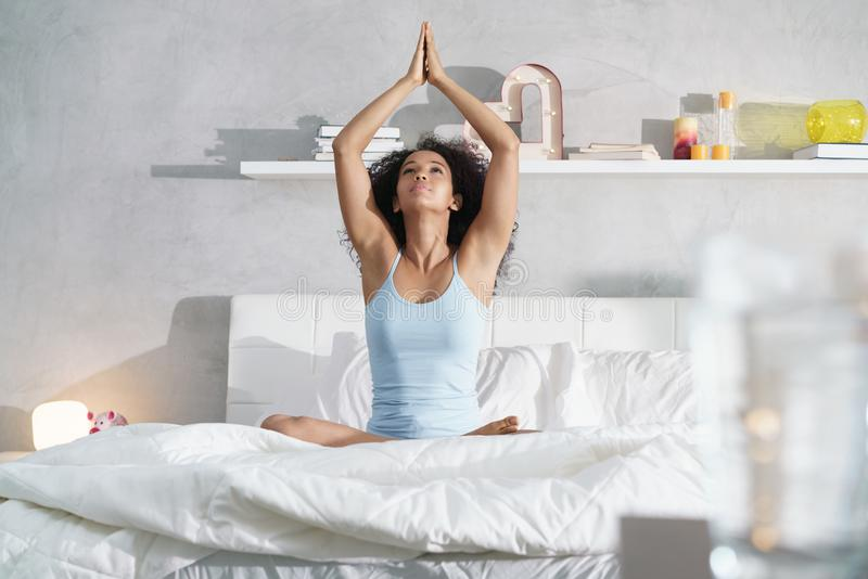 Junge Afroamerikaner-Frau, die Yoga im Bett nach Schlaf tut stockbild
