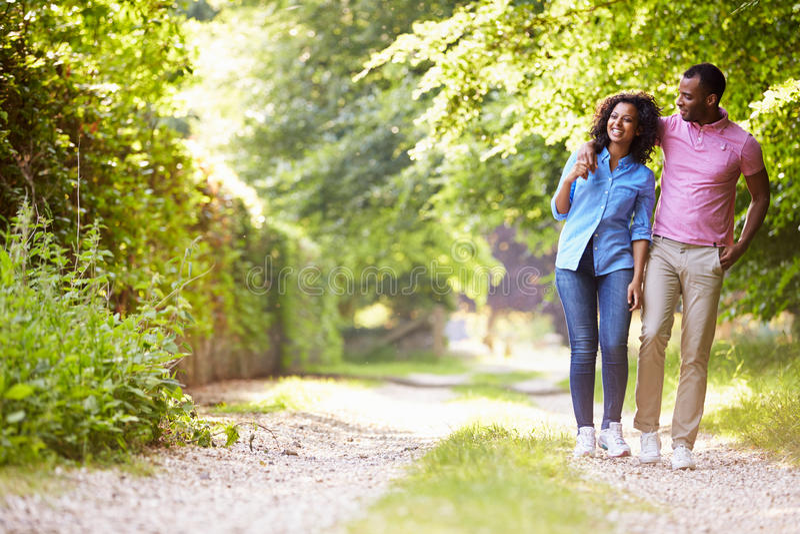 Junge Afroamerikaner-Paare, die in Landschaft gehen lizenzfreie stockfotos