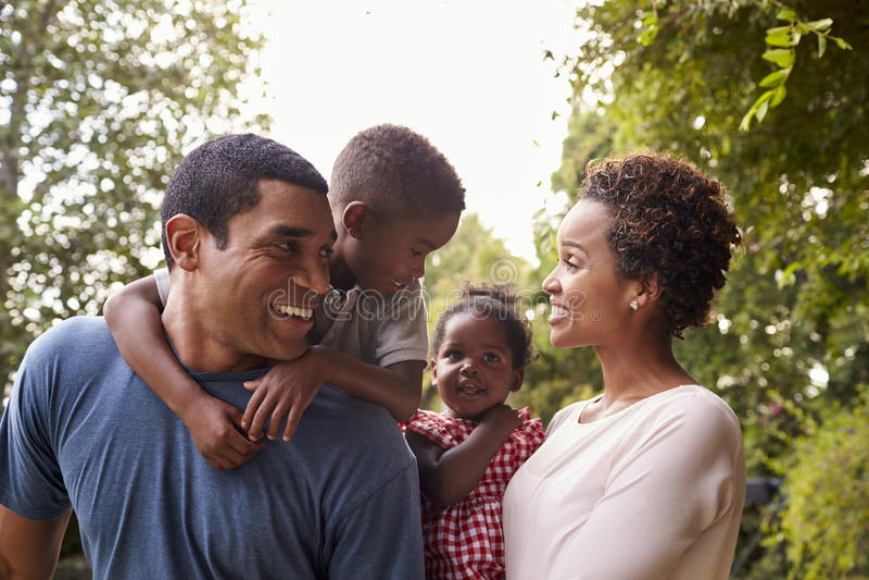 Junge Afroamerikanereltern, die Kinder im Garten tragen stockfotos