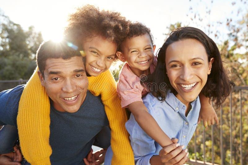 Junge Afroamerikanerelterneltern, die den Spaß huckepack trägt ihre Kinder im Garten und oben schaut zur Kamera, Abschluss haben lizenzfreies stockbild