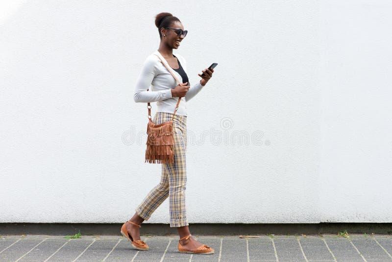 Junge Afroamerikanerfrau des Seitenporträts, die gegen weiße Wand mit Mobiltelefon geht stockbilder