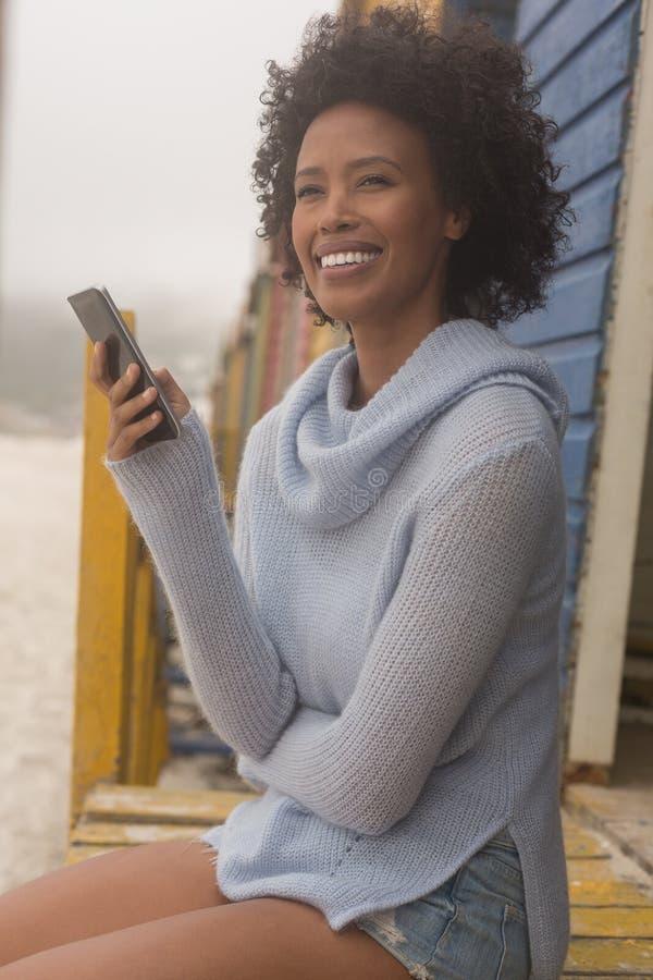 Junge Afroamerikanerfrau, die den Handy sitzt an der Strandhütte verwendet lizenzfreies stockfoto
