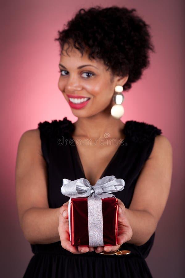 Junge Afroamerikanerfrau, die ein Geschenk anbietet lizenzfreie stockfotos