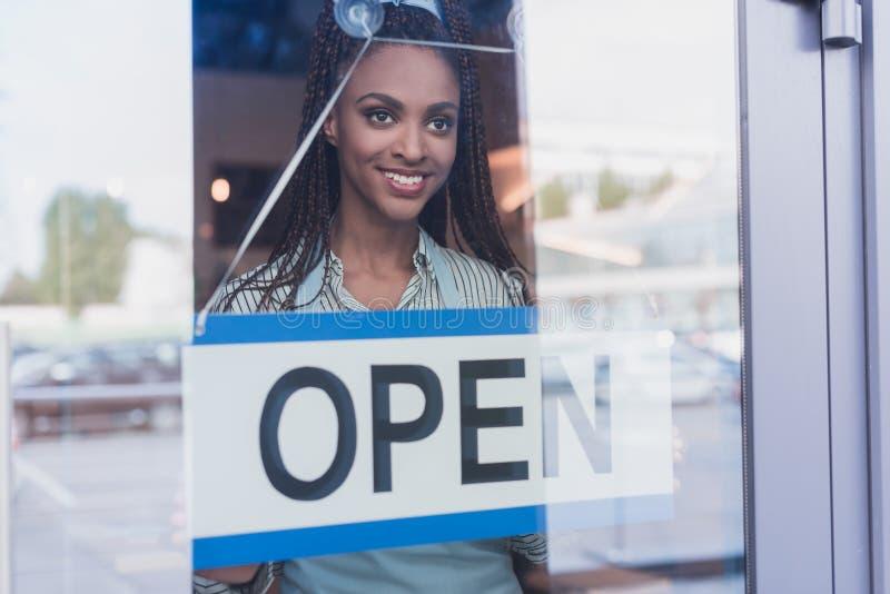 Junge Afroamerikanerfrau, die ein offenes Zeichen auf a hängt stockfoto