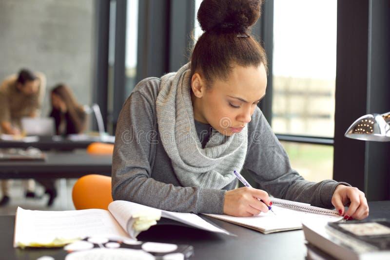 Junge Afroamerikanerfrau, die Kenntnisse nimmt stockfoto