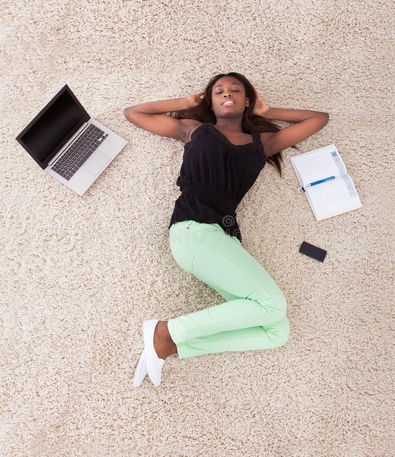 Junge Afroamerikanerfrau, die sich zu Hause auf Wolldecke entspannt lizenzfreies stockfoto