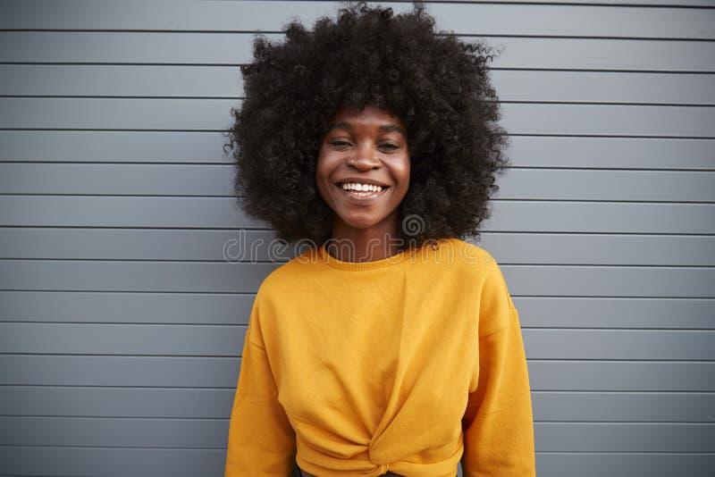 Junge Afroamerikanerfrau mit Afrostellung gegen die grauen Sicherheitsfensterläden, oben lächelnd zur Kamera, Abschluss stockfoto