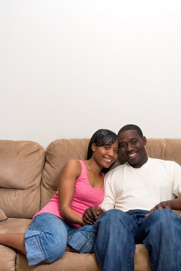 Junge Afroamerikanerpaare in ihrem Wohnzimmer lizenzfreie stockfotografie