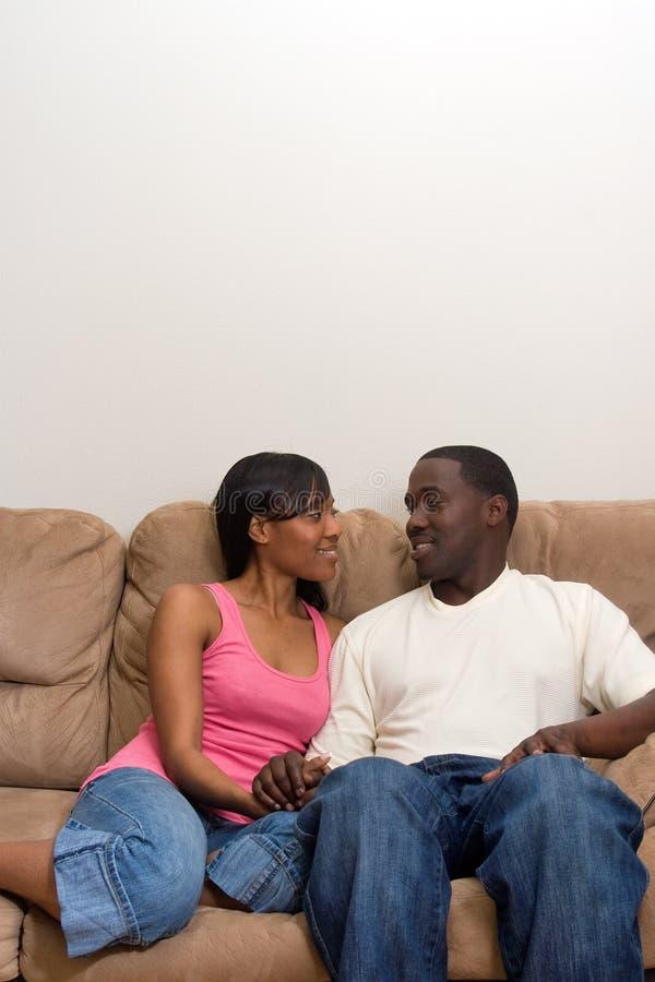 Junge Afroamerikanerpaare in ihrem Wohnzimmer lizenzfreie stockfotos