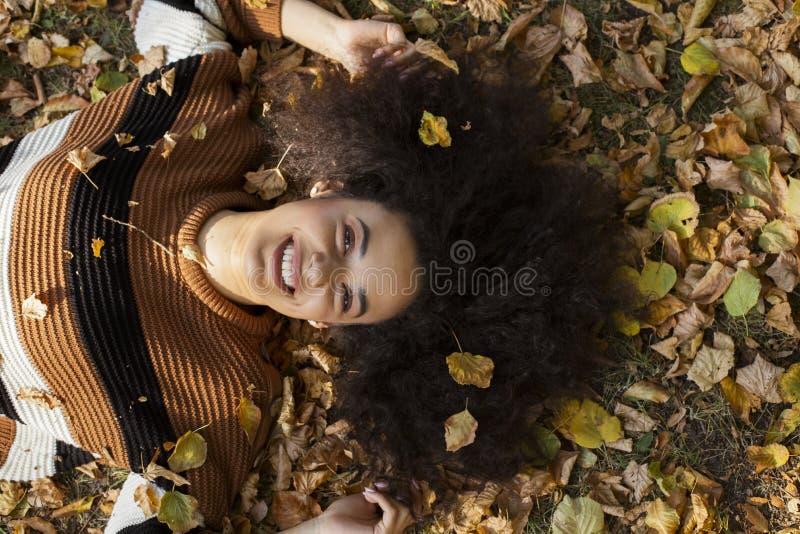 Junge afroe-amerikanisch Frau, die auf herbstlichen Bl?ttern im sonnigen Park liegt lizenzfreie stockbilder