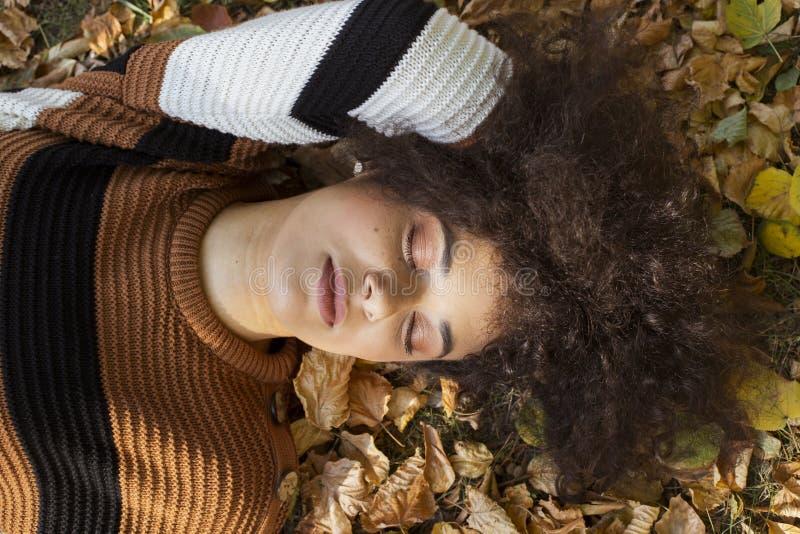 Junge afroe-amerikanisch Frau, die auf herbstlichen Bl?ttern im sonnigen Park liegt stockbilder