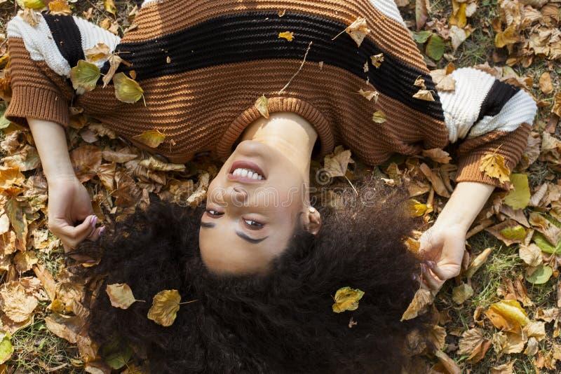 Junge afroe-amerikanisch Frau, die auf herbstlichen Bl?ttern im sonnigen Park liegt lizenzfreie stockfotos