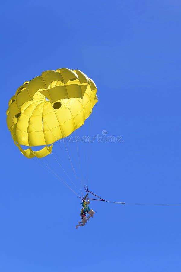 Junge aktive Paare, die das Fliegen mit Fallschirm, extreme Parasailingstätigkeit genießen stockfotografie