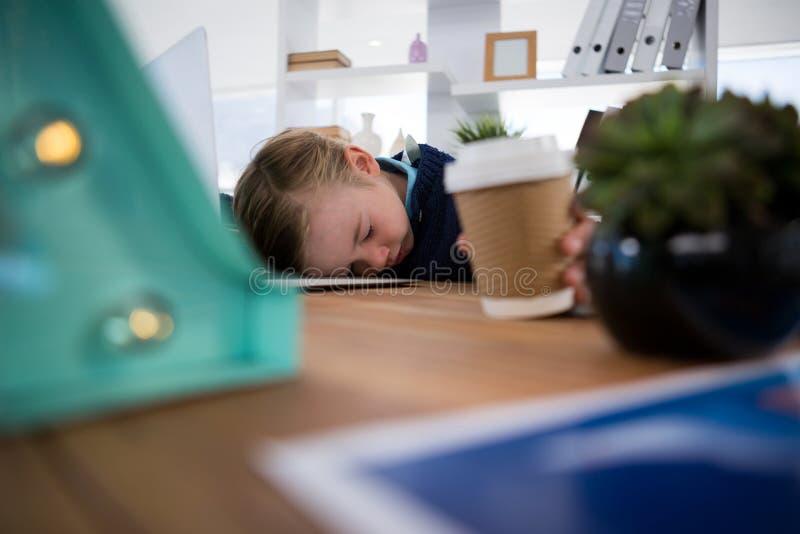 Junge als schlafender Unternehmensleiter beim Halten der Kaffeetasse lizenzfreies stockbild
