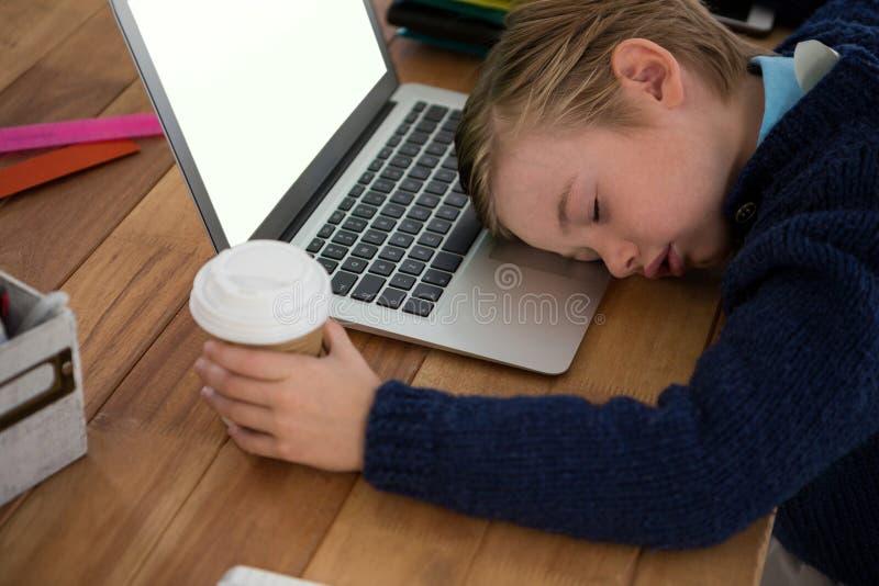 Junge als schlafender Unternehmensleiter beim Halten der Kaffeetasse lizenzfreie stockfotografie