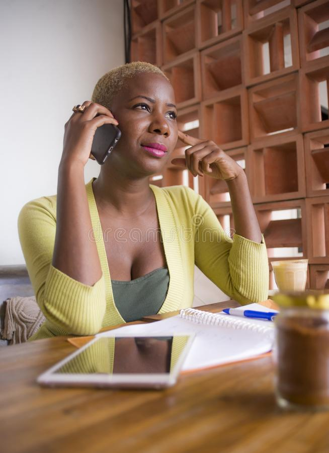 Junge amerikanische Geschäftsfrau des eleganten und schönen Schwarzafrikaners, die online mit Handy und digitaler Tablette am Kaf lizenzfreie stockfotos