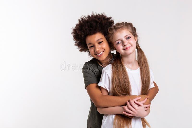 Junge angenehme Kinderreizendes zusammen schauen beim Umarmen lizenzfreies stockfoto