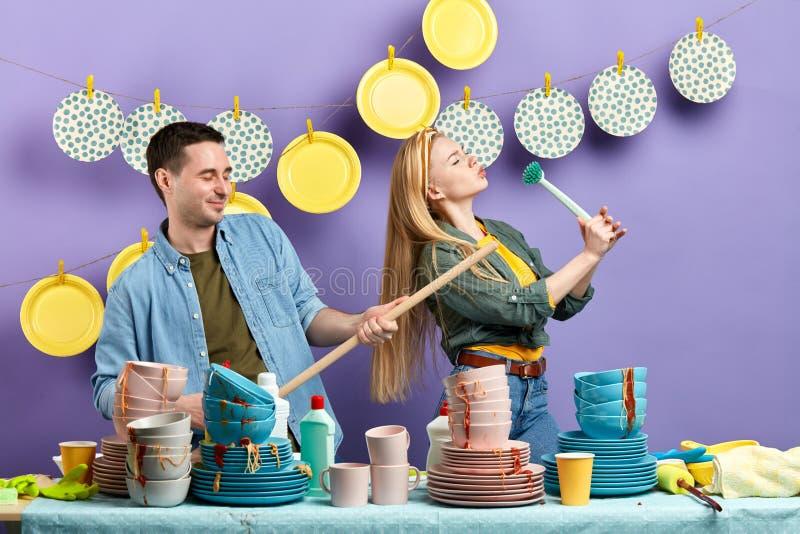 Junge angenehme Paare, die einen Rest beim Waschen von Platten und von Schalen haben stockfotografie