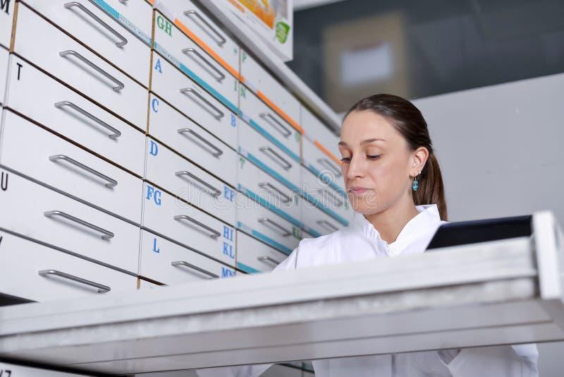 Junge Apothekerfrau, die nach Medizin sucht lizenzfreie stockfotos
