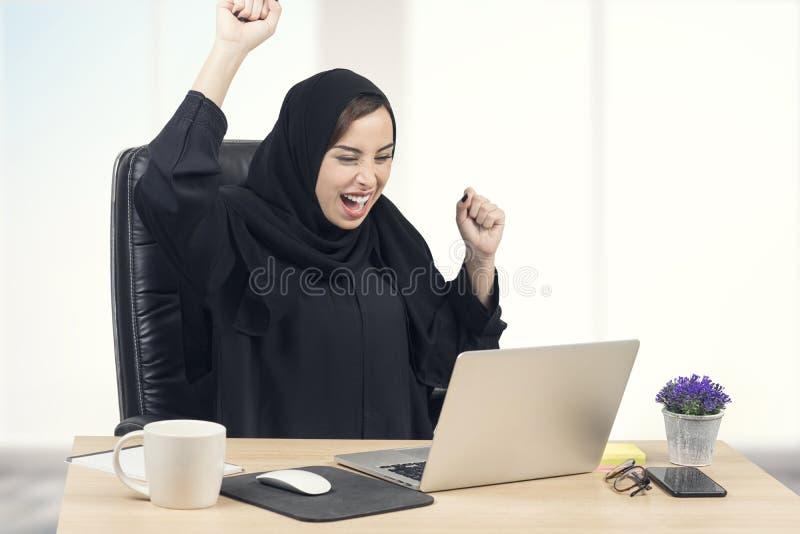 Junge arabische Geschäftsfrau, die Erfolg im Büro ausdrückt lizenzfreie stockbilder