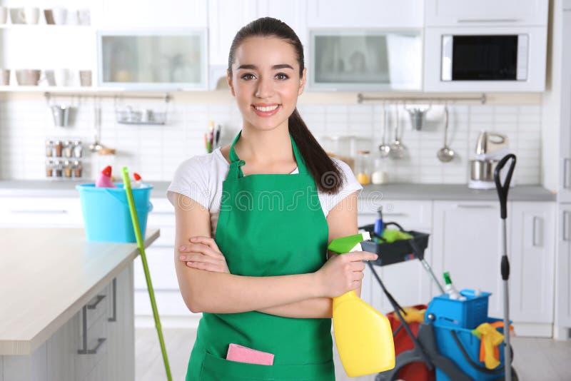Junge Arbeitnehmerin mit Flasche des Reinigungsmittels stockfoto