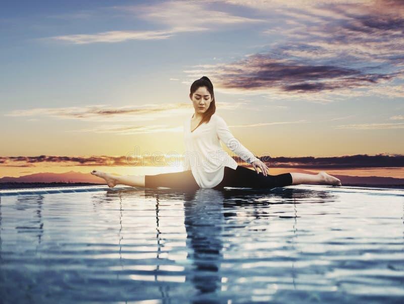 Junge Asiatin-übendes Yoga unter Sonnenaufgang, Weinlese getont stockbild