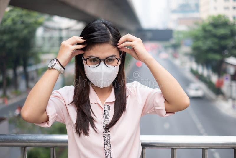 Junge Asiatin, die Atemmaske N95 pm2, zu schützen trägt und zu filtern Feinstaub 5 gegen Verkehr und Staubstadt stockfotos