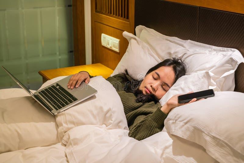 Junge Asiatin, die auf Bett nachdem dem Arbeiten an Laptop in der Geschäftsreise schläft stockfotografie