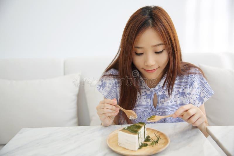 Junge Asiatin, die des Kreppkuchens des grünen Tees süße Nahrung isst stockbilder