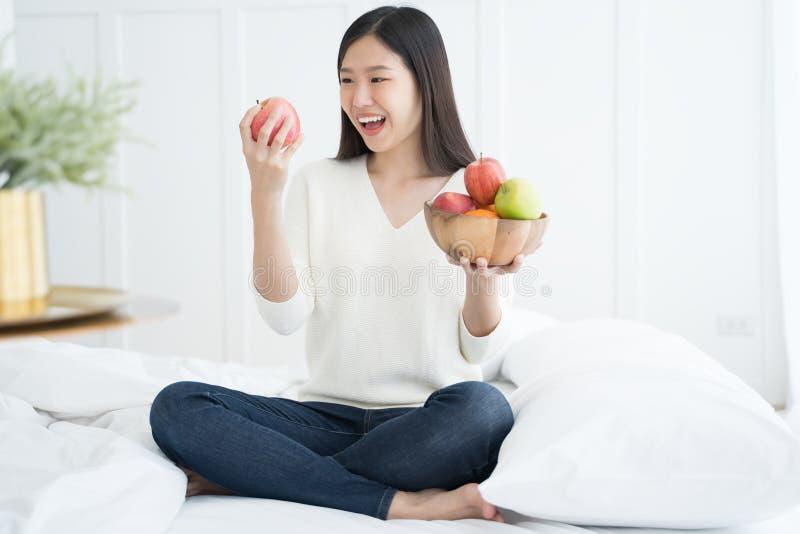 Junge Asiatin, die grünen Apfel und roten Apfel, zuhause Porträt zeigt lizenzfreie stockfotografie