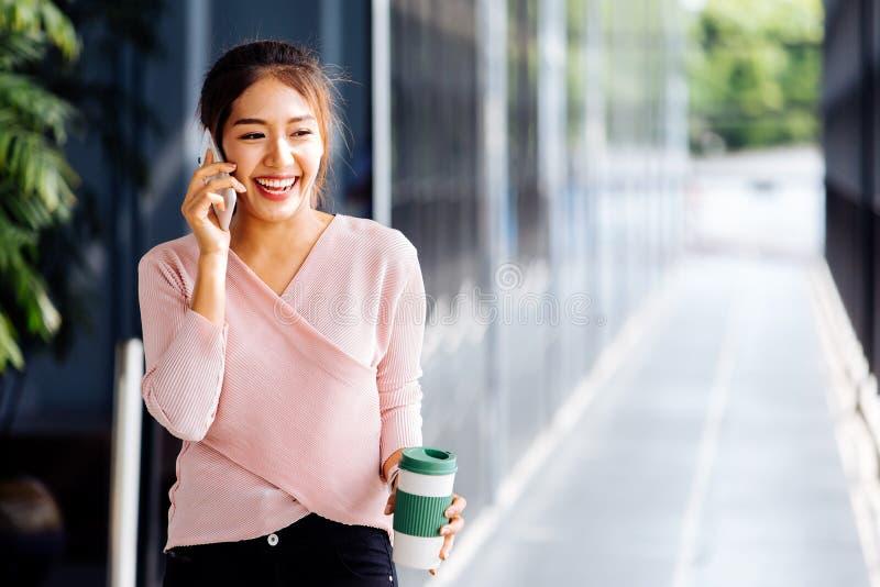 Junge Asiatin, die am Handy hält eine Kaffeetasse am Büroäußerhintergrund spricht lizenzfreies stockbild