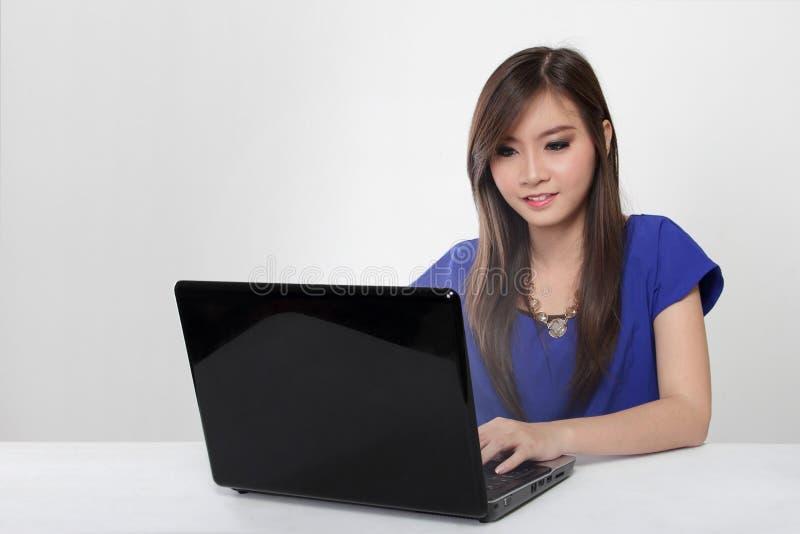 Junge Asiatin, die mit dem Laptop lokalisiert arbeitet lizenzfreie stockfotografie