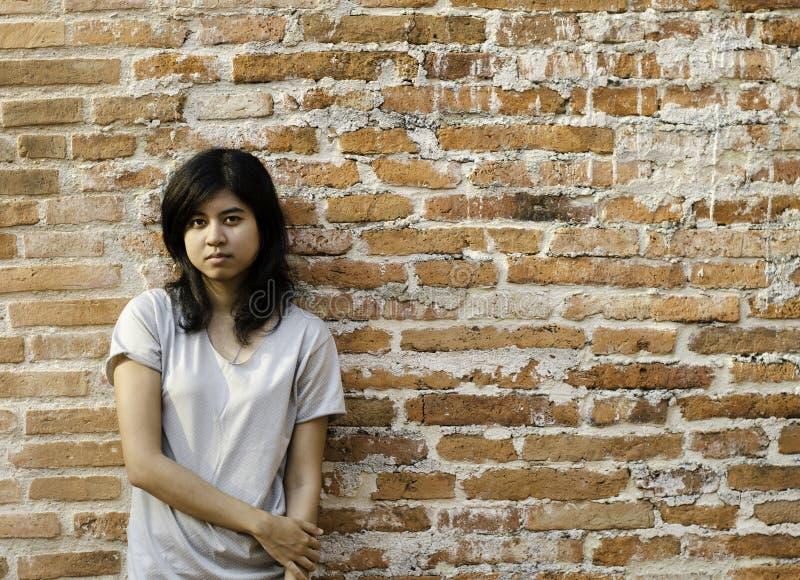 Junge Asiatin gegen eine Backsteinmauer lizenzfreie stockbilder