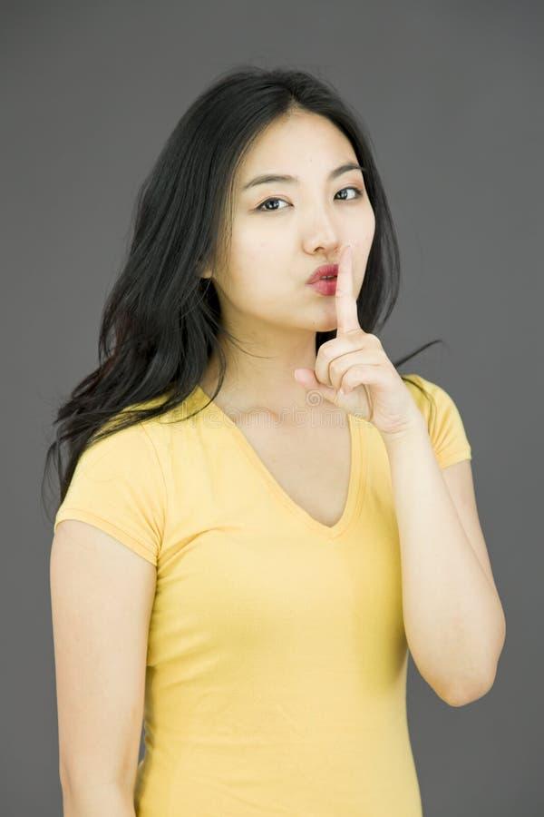 Junge Asiatin mit dem Finger auf Lippen lizenzfreie stockfotografie