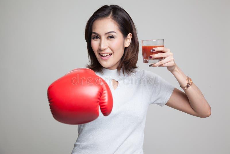 Junge Asiatin mit Tomatensaft und Boxhandschuh lizenzfreie stockfotografie