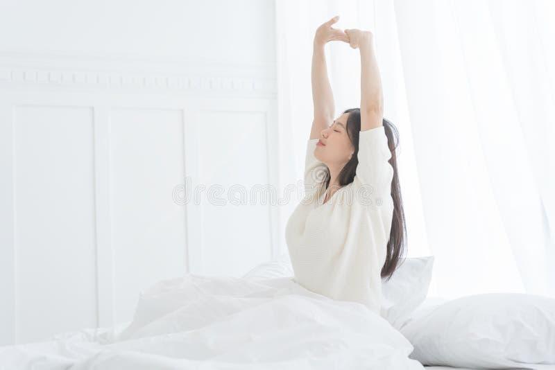 Junge Asiatin morgens sie ausdehnend in ihr Bett im Schlafzimmer stockbild